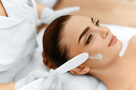 Protección de la piel. Primer De Cosmetician que aplica el cosmético hidratante crema en la cara de la mujer joven. Cara de belleza. Tratamiento de spa En Salón de Belleza. Tratamiento de belleza facial. Foto de archivo - 49277441