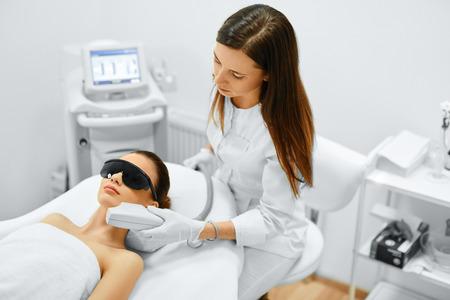 Cura della pelle. Giovane donna che riceve Trattamento facciale di bellezza, rimozione pigmentazione Alla Cosmetic Clinic. Intense Pulsed Light Therapy. IPL. Ringiovanimento, Foto Facial Therapy. Anti-invecchiamento Procedure. Archivio Fotografico - 49277448