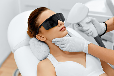 treatment: Face Care. Facial Laser Hair Removal. Beautician Giving Laser Epilation Treatment To Young Womans Face At Beauty Clinic. Body Care. Hairless Smooth And Soft Skin. Health And Beauty Concept. Stock Photo