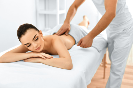 spa beauty: Spa Woman. Beauty Treatment. Beautiful Young Healthy Caucasian Girl Relaxing With Hand Massage Procedure In The Spa Salon. Masseur Massaging Her Back. Body Care. Skin Care, Wellness, Wellbeing.