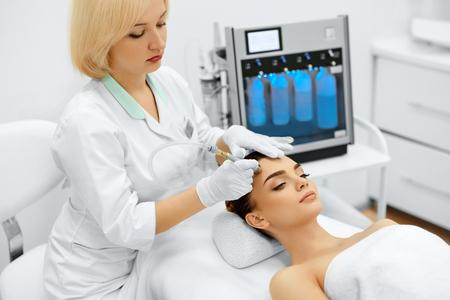 Gesichts-Hautpflege. Nahaufnahme der schönen Frau, die Diamant Microdermabrasion Peeling Behandlung in einem Beauty Spa Salon. Reinigung Verfahren. Kosmetologie. Lizenzfreie Bilder