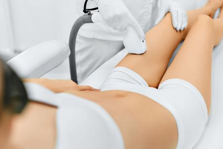 cuerpo humano: Cuidado corporal. Piernas depilación láser. Esteticista quitar el pelo de la pierna de la mujer joven. Depilación Láser Tratamiento En la Clínica de belleza cosmética. Piel tersa y suave sin pelo. Salud Y Belleza Concept. Foto de archivo