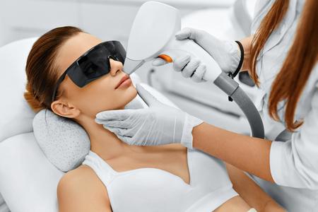 Cura del viso. Viso Depilazione laser. Estetista dà fronte Laser Epilazione Trattamento alla giovane donna di At Beauty Clinic. Cura del corpo. Hairless liscia e morbida pelle. Salute e Bellezza Concept.