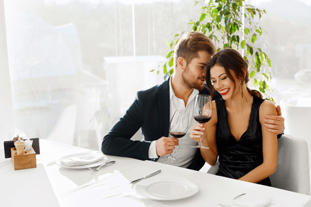 dating and romance: Love. Happy Romantic Smiling Couple Having Dinner, Embracing, Drinking Wine, Celebrating Holiday, Anniversary Or Valentines Day In Gourmet Restaurant. Romance, Relationships Concept. Celebration