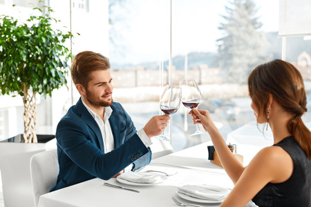 dinner date: Celebration. Happy Romantic Couple In Love Cheering With Glasses Of Red Wine, Having Dinner In Luxury Gourmet Restaurant, Celebrating Anniversary Or Valentines Day. Romance, Relationship. Cheers Stock Photo
