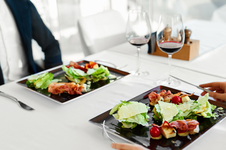 浪漫: 健康食品食用。特寫年輕夫婦的凱撒沙律配烤雞,蔬菜和奶酪餐豪華美食餐廳。人們在日期。浪漫的晚餐或午餐,飲食觀念
