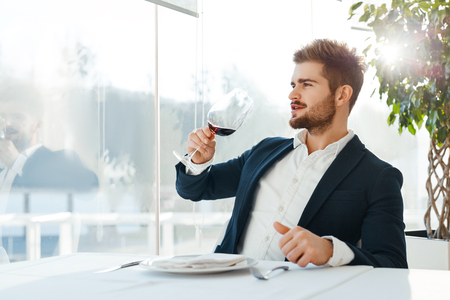 Wine. Closeup Of Beautiful Young Man Tasting A Glass Of Red Wine While Looking Through The Window. Businessman Drinking Alcohol In Luxury Gourmet Restaurant. Success Celebration Dinner Concept