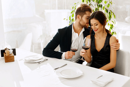 Love. Happy Romantic Smiling Couple Having Dinner, Embracing, Drinking Wine, Celebrating Holiday, Anniversary Or Valentine's Day In Gourmet Restaurant. Romance, Relationships Concept. Celebration Foto de archivo