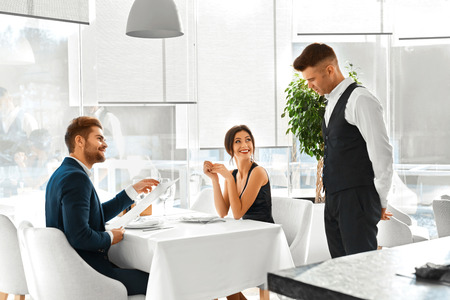 Romantic Dinner. Happy Smiling Couple In Love Reading Menu And Ordering Food To Waiter In Luxury Gourmet Restaurant. People Celebrating Anniversary Or Valentine's Day. Romance, Relationships Concept.