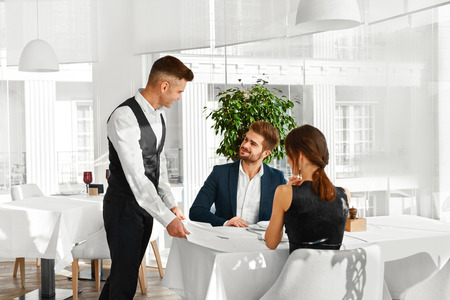 Dinner In Restaurant. Waiter Serving Happy Romantic Young Couple In Love. Cheerful People Making Orders, Celebrating Anniversary Or Valentines Day. Love, Romance, Relationships Concept. Banco de Imagens