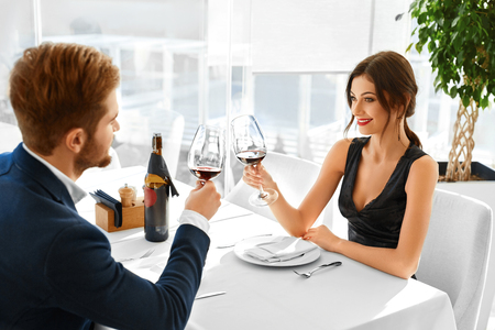lovely women: Celebration. Happy Romantic Couple In Love Cheering With Glasses Of Red Wine, Having Dinner In Luxury Gourmet Restaurant, Celebrating Anniversary Or Valentines Day. Romance, Relationship. Cheers Stock Photo