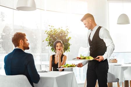personas festejando: Pareja feliz en el amor que cena romántica en restaurante Gourmet de lujo. Camarero de suministro de comida. La gente que celebra aniversario o el día de San Valentín. Romance, relación de conceptos. Comida sana Alimentos.