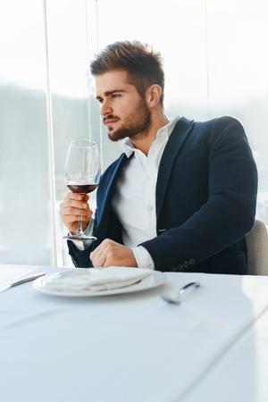 tomando vino: Beber. Primer De elegante hermosa del hombre joven que bebe el vino rojo que se sienta en restaurante Gourmet de lujo. El hombre de negocios de relajación y mirando por la ventana. Concepto de éxito cena de celebración