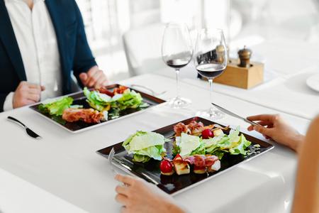 Gesundes Essen. Nahaufnahme Der Junge Paare, die Caesar-Salat mit gebratenem Huhn, Gemüse und Käse für die Mahlzeit in der Luxus-Gourmet Restaurant. Menschen am Datum. Romantisches Abendessen oder Mittagessen, Diät-Konzept