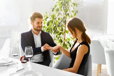 matrimonio feliz: Amor. Pareja relación romántica. Primer Del Hombre hermoso que hace la proposición de matrimonio a la mujer hermosa con el anillo de compromiso de diamantes en el lujo Restaurante Gourmet. Boda, concepto romances. Foto de archivo