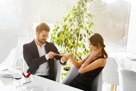 matrimonio feliz: Relaciones. Pareja romántica en el amor decidieron casarse. Primer Del Hombre va a proponer matrimonio a la mujer con anillo de compromiso de diamantes en el lujo Restaurante Gourmet. Boda, concepto romances.