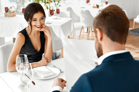 Romantic Couple In Love Having Dinner In Luxury Gourmet Restaurant. Happy Beautiful Lovely People Reading Menu, Choosing Food, Celebrating Anniversary Or Valentines Day. Romance And Relationships.