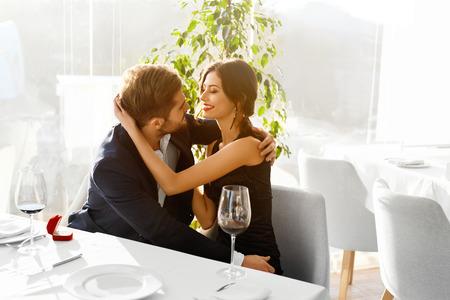 haciendo el amor: Relaciones. Pareja romántica en el amor decidieron casarse. Primer Del Hombre va a proponer matrimonio a la mujer con anillo de compromiso de diamantes en el lujo Restaurante Gourmet. Boda, concepto romances.