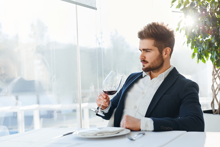 model male: Drink. Closeup Of Elegant Handsome Young Man Drinking Red Wine Sitting In Luxury Gourmet Restaurant. Businessman Relaxing And Looking Through The Window. Success Celebration Dinner Concept Stock Photo