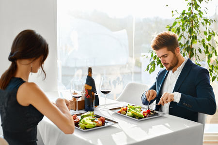 Gezonde Voeding eten. Close-up van jonge paar Caesar salade met gebraden kip, groenten en kaas voor Maaltijd in Luxury Gourmet Restaurant. Mensen Op Date. Romantisch diner of lunch, dieet Concept Stockfoto