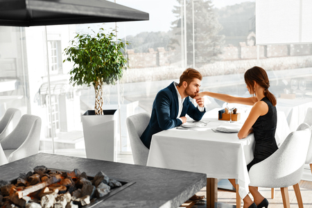 Happy Couple In Love Having Romantic Dinner In Gourmet Restaurant. Man Kissing Lovely Woman's Hand. Elegant People On A Date, Celebrating Anniversary Or Valentine's Day. Romance, Relationship Concept. Stock Photo
