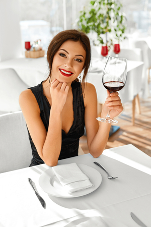 dinner date: Romantic Dinner. Closeup Of Beautiful Elegant Sexy Young Woman Drinking Red Wine In Luxury Gourmet Restaurant. Happy Smiling Girl On A Date. Drink. Celebration. Stock Photo