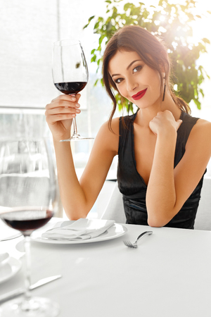 wine glass: Romantic Dinner. Closeup Of Beautiful Elegant Sexy Young Woman Drinking Red Wine In Luxury Gourmet Restaurant. Happy Smiling Girl On A Date. Drink. Celebration. Stock Photo