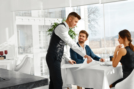 servings: Dinner In Restaurant. Waiter Serving Happy Romantic Young Couple In Love. Cheerful People Making Orders, Celebrating Anniversary Or Valentines Day. Love, Romance, Relationships Concept. Stock Photo