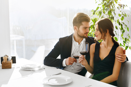 valentines: Love. Happy Romantic Smiling Couple Having Dinner, Embracing, Drinking Wine, Celebrating Holiday, Anniversary Or Valentines Day In Gourmet Restaurant. Romance, Relationships Concept. Celebration
