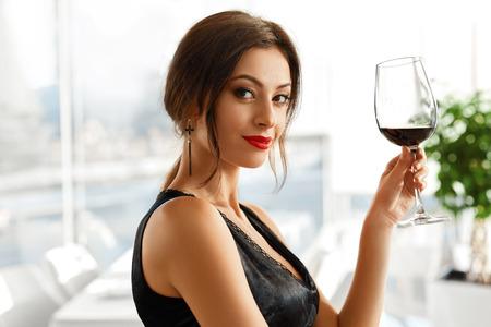 tomando vino: Beber vino. Retrato de atractivo feliz sonriente mujer joven con una copa de vino tinto. Cena romántica en restaurante Gourmet de lujo. Sexy chica elegante celebra día de fiesta. Celebracion.
