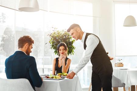 романтика: Счастливая пара в любви с романтическим ужином в роскошных ресторане изысканной кухни. Кельнер сервировки еды. Люди Празднование годовщины или День святого Валентина. Романтика, Отношения Концепция. Здоровое питание питание. Фото со стока