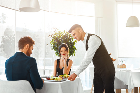 serving: Happy Couple In Love Having Romantic Dinner In Luxury Gourmet Restaurant. Waiter Serving Meal. People Celebrating Anniversary Or Valentines Day. Romance, Relationship Concept. Healthy Food Eating.