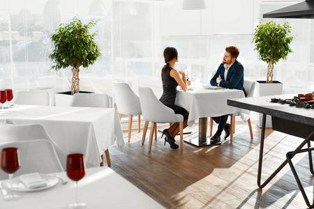 Paar In Liefde. Gelukkige Glimlachende Elegante Jonge mensen vieren Dag van de verjaardag of Valentijnsdag en met romantisch diner of lunch samen in Gourmet Restaurant. Romantiek, relaties Concept.