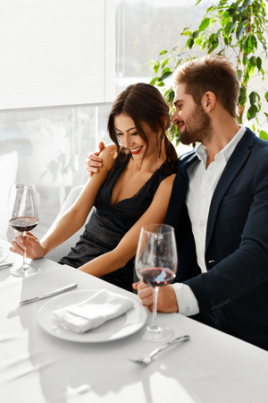 lovely women: Couple In Love. Happy Romantic Smiling Elegant People Having Dinner, Drinking Wine, Celebrating Holiday, Anniversary Or Valentines Day In Gourmet Restaurant. Romance, Relationships Concept. Stock Photo
