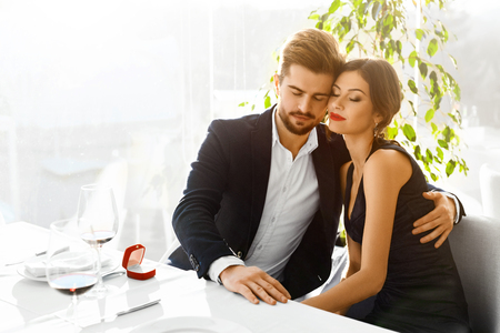 proposal of marriage: Relationships. Romantic Couple In Love Decided To Get Married. Closeup Of Man Is Going To Propose Marriage To Woman With Engagement Diamond Ring In Luxury Gourmet Restaurant. Wedding, Romance Concept. Stock Photo