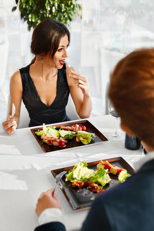 almuerzo: Comida sana Alimentos. Detalle de la pareja joven que tiene ensalada C�sar con pollo asado, verduras y queso para la comida en restaurante Gourmet de lujo. La gente de la fecha. La cena rom�ntica o el almuerzo, el concepto de dieta