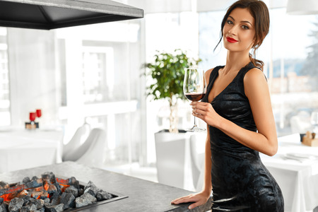 mujer elegante: Beber vino. Retrato de atractivo feliz sonriente mujer joven con una copa de vino tinto. Cena romántica en restaurante Gourmet de lujo. Sexy chica elegante celebra día de fiesta. Celebracion.
