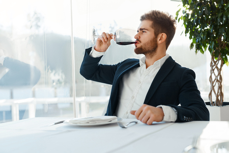 successful man: Wine. Closeup Of Beautiful Young Man Tasting A Glass Of Red Wine While Looking Through The Window. Businessman Drinking Alcohol In Luxury Gourmet Restaurant. Success Celebration Dinner Concept