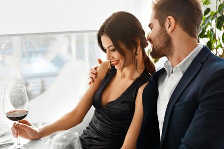 lifestyle: Couple amoureux. Happy romantiques Personnes Élégantes Sourire dîner, boire du vin, Célébration de vacances, le jour de l'anniversaire ou la Saint-Valentin en restaurant gastronomique. Romance, Relations Concept.