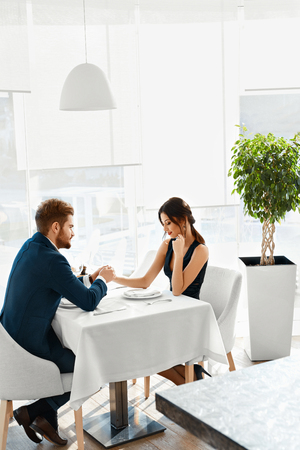 restaurant dining: Romantic Dinner. Happy Lovely Couple Celebrating Anniversary Or Valentines Day Together In Luxury Fancy Gourmet Restaurant. Love, Romance, Relationships Concept. Stock Photo