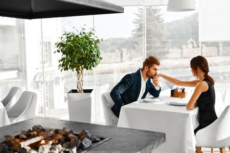 Glückliche Paare in der Liebe Romantisches Abendessen im Gourmet-Restaurant zu haben. Man Kissing Schöne Hand der Frau. Elegante Menschen auf ein Datum, Feiern Jahrestag oder Valentinstag. Romance, Beziehung Konzept.