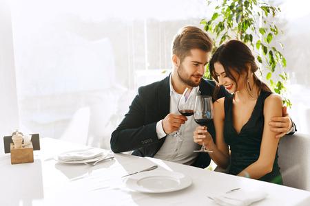 romance: Amor. Pareja feliz, sonriente Tener Cena romántica, Abrazar, Vino de consumición, vacaciones Celebración, Día de San Valentín Aniversario O En Gourmet Restaurant. Romance, Relaciones Concept. Celebración