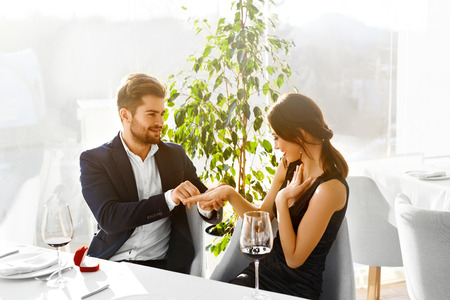 propose: Relationships. Romantic Couple In Love Decided To Get Married. Closeup Of Man Is Going To Propose Marriage To Woman With Engagement Diamond Ring In Luxury Gourmet Restaurant. Wedding, Romance Concept. Stock Photo