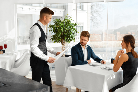Dinner In Restaurant. Waiter Serving Happy Romantic Young Couple In Love. Cheerful People Making Orders, Celebrating Anniversary Or Valentines Day. Love, Romance, Relationships Concept. Stock Photo