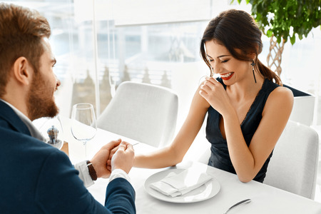 romantic love: Couple In Love. Happy Smiling Elegant Young People Celebrating Anniversary Or Valentines Day And Having Romantic Dinner Or Lunch Together In Gourmet Restaurant. Romance, Relationships Concept. Stock Photo