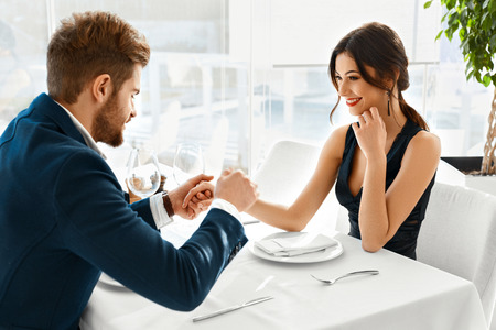 Couple In Love. Happy Smiling Elegant Young People Celebrating Anniversary Or Valentine's Day And Having Romantic Dinner Or Lunch Together In Gourmet Restaurant. Romance, Relationships Concept. photo