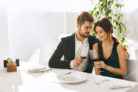 романтика: Влюбленная пара. Счастливые Романтический Smiling Элегантные люди обедали, пили вино, празднуя отпуска, дня годовщины или Валентина в ресторане изысканной кухни. Романтика, Отношения Концепция.