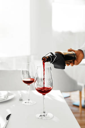 Drink. Closeup Of Mans Hand Pouring Red Wine From Bottle Into Wine Glass In A Restaurant. Alcohol Drinks. Celebration And Lifestyle.