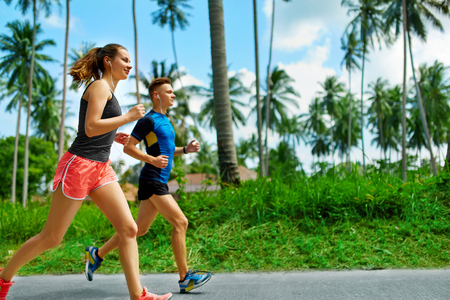 couple outdoor: Fit Athletic Couple Running On Road, Training For Marathon.