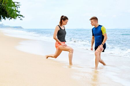 personas trotando: Fit Athletic People Stretching Legs, Exercising Before Jogging On Beach. Foto de archivo
